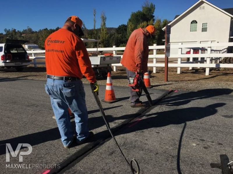 A road crew prepares a wide crack for GAP Mastic repair by cleaning it with a blower.