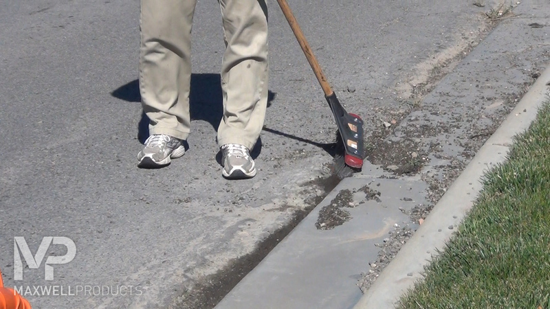 A road crew uses a wire broom to clean and remove loose pavement.