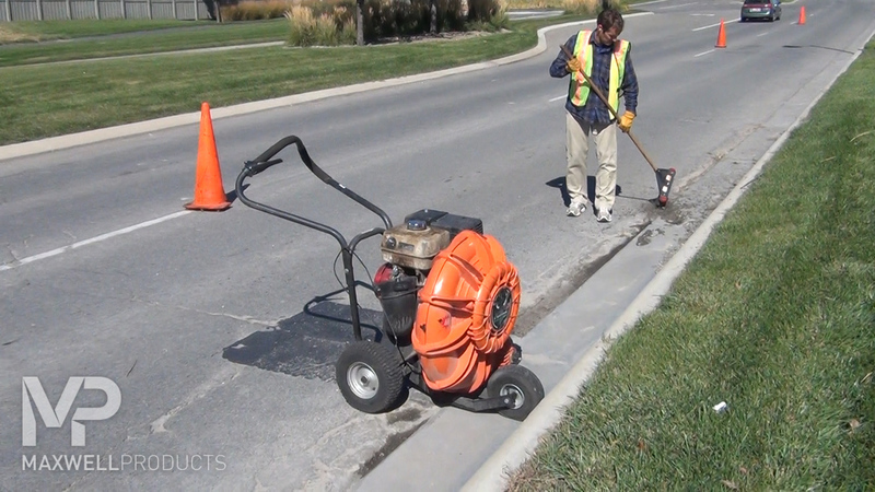 A road worker cleans and preps an area of pavement with a blower and wire brush.