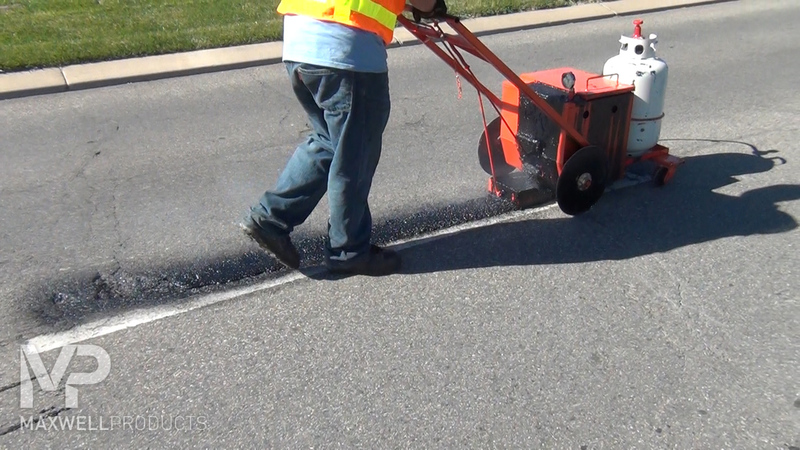 A road crew applies GAP Mastic with a 10-gallon pour pot and hot box.