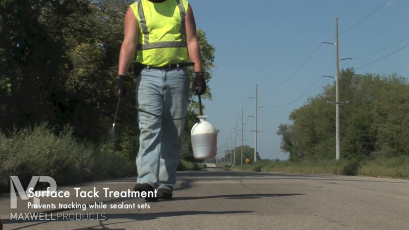 Road crew applies a surface tack treatment to prevent tracking while sealant cures.